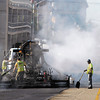 "Heat and smoke rise from the ""hot-in-place"" paving method being used by Gallagher Asphalt Corp. as they re-surface Meridian Street Tuesday.  The method heats up the old asphalt, breaks it up, then mixes it with fresh oil and materials and spreads it back down on the road in one pass."