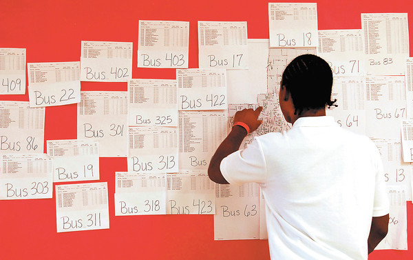 Anderson High School junior Bradrick Peak checks the bus listings to see which school bus is his bus to ride on the first day of classes for ACS.