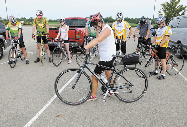 Bicyclists bow their heads in prayer before leaving on a ride from Madison Park Church of God on Tuesday. The church hosts a weekly bike ride.