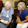 From left, Maxine Jones and her daughter Jackie Grimes look at the book of six word memoirs by Bethany Pointe residents during a book release and reception on Thursday.