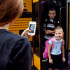 Melanie Coverdale takes a photo of her daughter Arianna, 5, getting off the school bus at Killbuck School Wednesday on her first day of school as a kindergartner.