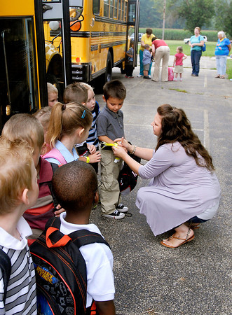 Parent volunteer Alli Robison puts a wrist ban on the student as they get off the school bus Wednesday morning at Killbuck School.  The wrist bans had the students name, teacher, and bus number so they could make their way around on the first day of school.