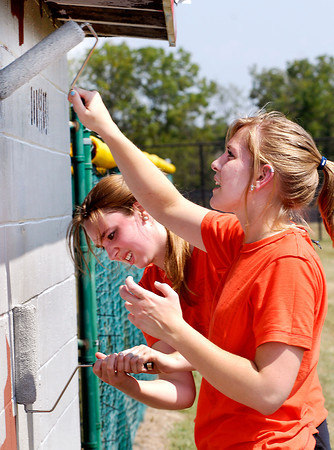 AU freshmen Kira Crites, from Westfield, Ind., and Victoria Hooley, from La Porte, Ind., paint the Anderson High School baseball dugout Friday afternoon as part of their new-student orientation performing community service projects.
