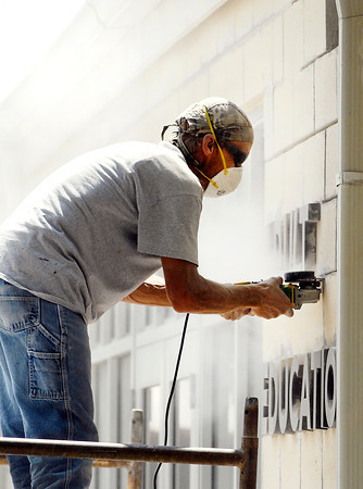 Jeff Caudill, of S.A. Boyce, Inc. of Muncie, kicks up a cloud of dust as he grinds out a bad mortar joint on one of the buildings at the Hopewell Center on south Main Street in Anderson Monday afternoon.  The company was doing tuck pointing on all the block then painting the entire facility.