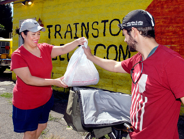 Sandra Davisson, owner of The Trainstop Deli, gives an order to Collin Rudkin of Jack Rabbit Couriers for delivery.