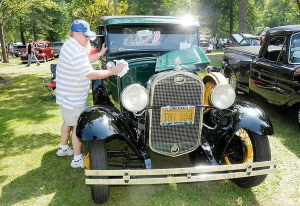 """Don Knight/The Herald Bulletin<br /> Dave Williams of Upland wipes down his 1931 Model A Ford during the Elwood Glass Festival on Saturday. """"Wanted a Model A since I was a little kid, now I have two,"""" Williams said."""