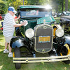 "Don Knight/The Herald Bulletin<br /> Dave Williams of Upland wipes down his 1931 Model A Ford during the Elwood Glass Festival on Saturday. ""Wanted a Model A since I was a little kid, now I have two,"" Williams said."