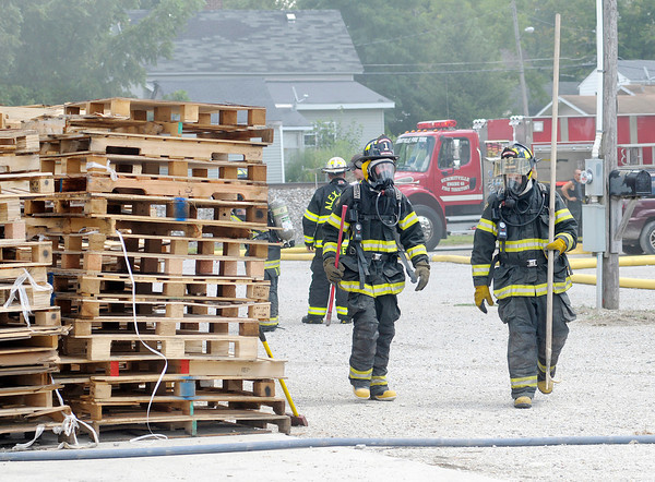Don Knight/The Herald Bulletin<br /> Summitville firefighters walk towards the entrance of Hurt's Pallet Repair and Sales to overhaul a fire scene at the factory in Summitville on Saturday.