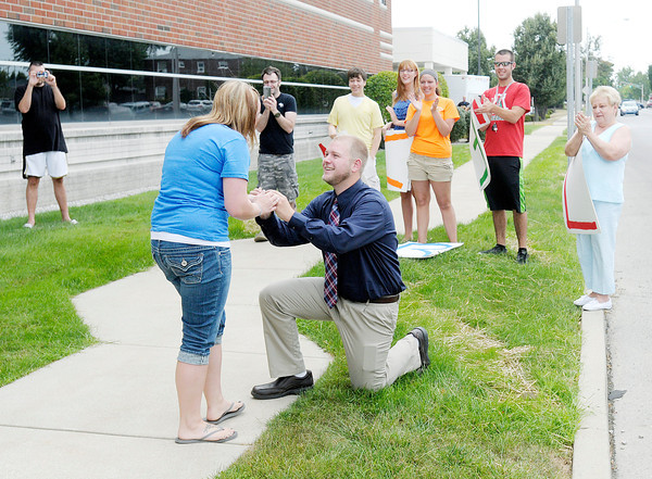 Don Knight/The Herald Bulletin<br /> With help from family and friends Drew Fox proposes to Danielle Finney outside the Erskine Medical Office Building where she works on Wednesday. Fox had family and friends hold up signs asking Danielle to marry him while her co-workers coaxed Danielle to look out the window. She said yes.