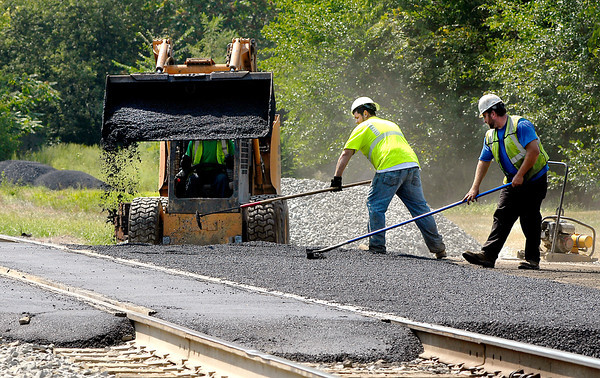 Workers spread out the asphalt on the Madison Ave. railroad crossing Friday afternoon as they finish up redoing the crossing.  Madison Ave. should be reopened Saturday morning after being closed since Tuesday.