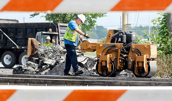 Workers lay down fresh asphalt on the east approach to the west 53rd Street railroad crossing Friday afternoon.  CSX Railroad as been working on repairing the crossing and plans to have it open for this weekend & Monday then closed through next Friday to finish repairs.
