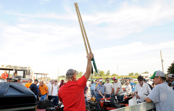 Don Knight/The Herald Bulletin<br /> A post hole digger is hoisted in the air so bidders can see what's currently up for bid as hundreds gathered at Mort's Auction Field on U.S. 36 for their Fall consignment auction on Saturday. Jeff Boone and Associates Auctioneers ran the event which included three auction rings.