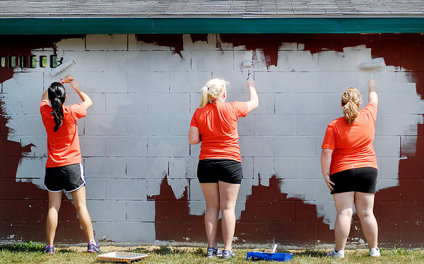 These AU students paint the Anderson High School baseball dugouts Friday afternoon as part of their new-student orientation performing community service projects.