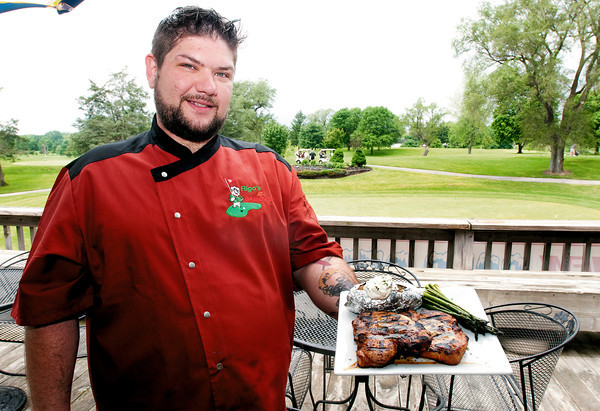Rigo's head chef Daniel Voyles holds an entree of Mesquite Marinated  Pork Chops with a baked potato and the vegetable of the day with at Grandview.