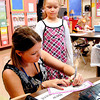 Kindergarten teacher Jessica Buell makes out a desk nametag for new student <br /> Isabella Page on the first day of school for ACS.