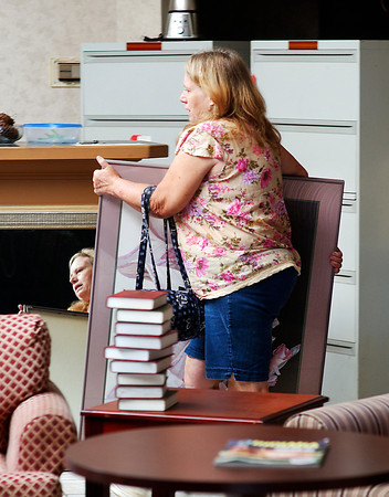 Bonnie Atkins, from Wilkinson, Ind., carries a large painting through the maze of items for sale at the former Garden Hotel's liquidation sale Tuesday as she looks for more bargains.