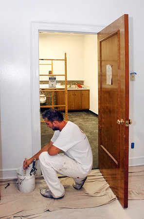 Patrick Plichta, of Holt Construction, Indianapolis, paints the trim in one of the rooms of the old Guilkey Funeral Home Friday as Legacy is remodeling the facility and plans to open the funeral home this fall.