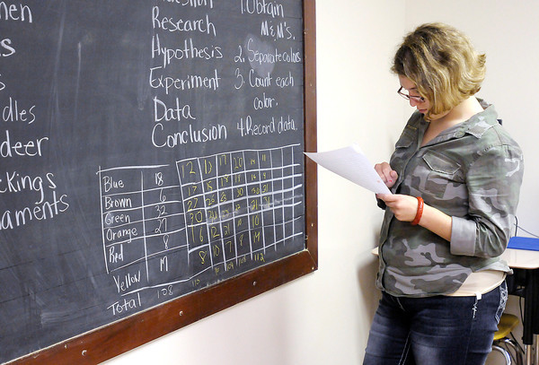 Don Knight/The Herald Bulletin<br /> Shelby McClure, 16, records her results from counting the number and color of M&Ms candies in a package as students in Sheila Arvin's Earth and Space Science class end their first day with a fun assignment at Anderson Christian School on Monday.