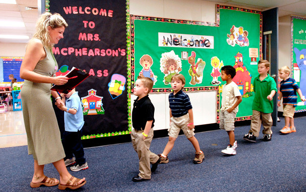Killbuck School kindergarten teacher Jamey Knight takes her class for a walk around their new environment on their first day of school Wednesday.
