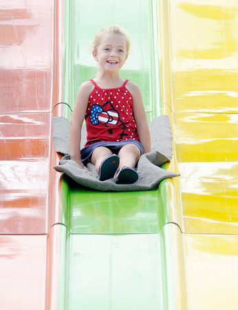 Don Knight/The Herald Bulletin<br /> Ella Foust, 6 rides the Super Slide on the midway at the Elwood Glass Festival on Saturday.