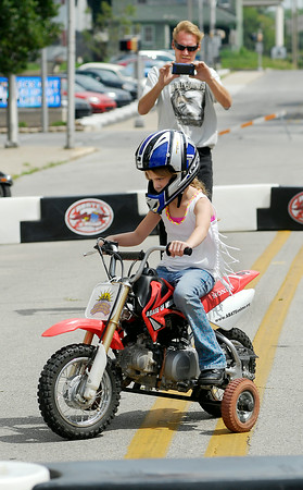 John P. Cleary | The Herald Bulletin<br /> Chloe Eastwood, 7, gets her first experience riding a motorcycle as dad, Chad Eastwood, takes her photo at the ABATE of Indiana's Tiny Tots Motorcycle Adventure during the City Wide Community Day at Dickmann Town Square.