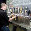 Don Knight | The Herald Bulletin<br /> Scott Reese pours a beer flight, four varieties in six ounce glasses, as Hoosier Park celebrated the opening of their Dan Patch Brewhouse on Thursday. The Brewhouse keeps ten local brews on tap plus a larger selection of Indiana beer and wine in bottles. Business and community leaders were invited to the Thursday ribbon cutting, the Brewhouse opens to the public today.