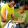 John P. Cleary | The Herald Bulletin<br /> Wade Jackson Jr. helps his son Martez Jackson, 5, see all the school supplies that are in the bag he received at the annual Ollie Dixon Back-to-School Parade and Picnic Saturday.
