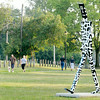 Don Knight | The Herald Bulletin<br /> Walkers walk past a Walking Man sculpture located on the walking trails at Shadyside Park on Thursday. After a stormy morning skies cleared in time for an evening walk.