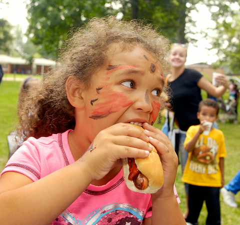 John P. Cleary | The Herald Bulletin<br /> Mason Taylor, 5, takes a big bite from her hotdog Saturday while enjoying the annual Ollie Dixon Back-to-School Parade and Picnic Saturday at Jackson Park.
