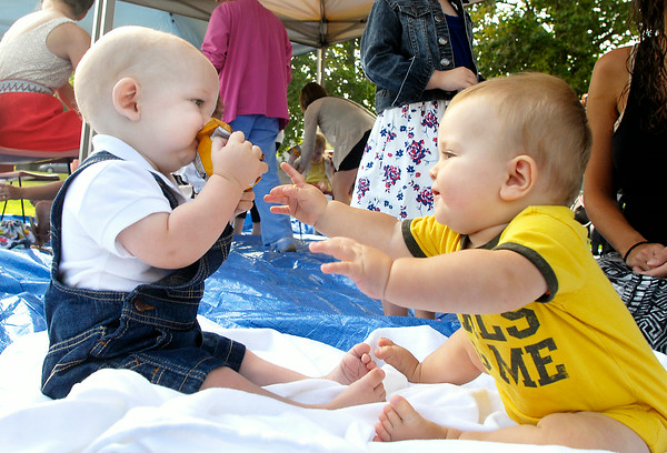 John P. Cleary   The Herald Bulletin<br /> Gabriel Blanton, right, 18 months, reaches out for the bag of cookies that Ivan Surface, 7 months, has hoping for some as they played during Community Hospital Anderson's Mommy Monday event Monday morning.  The cousins were at the event with their mothers and family interacting with other young children besides each other.