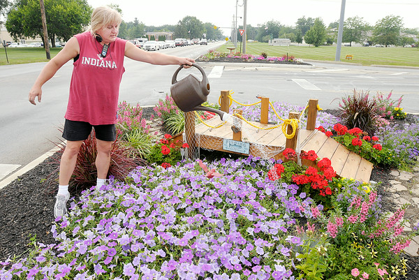 Don Knight | The Herald Bulletin<br /> Theresa Timmons tends to the flower garden in the traffic median at 53rd and Main Streets on Wednesday afternoon. Timmons works for the Salt Shop, the sponsor of the two median gardens at 53rd and Main.