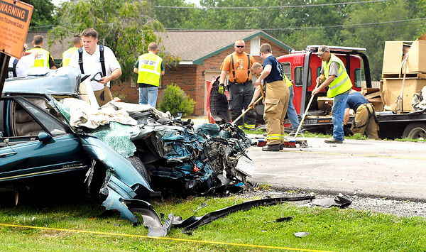 John P. Cleary | The Herald Bulletin<br /> workers cleanup debris from the scene of a fatal head-on collision involving a car and a flatbed truck in the 9100 block of North Indiana 37 near Elwood Thursday morning.