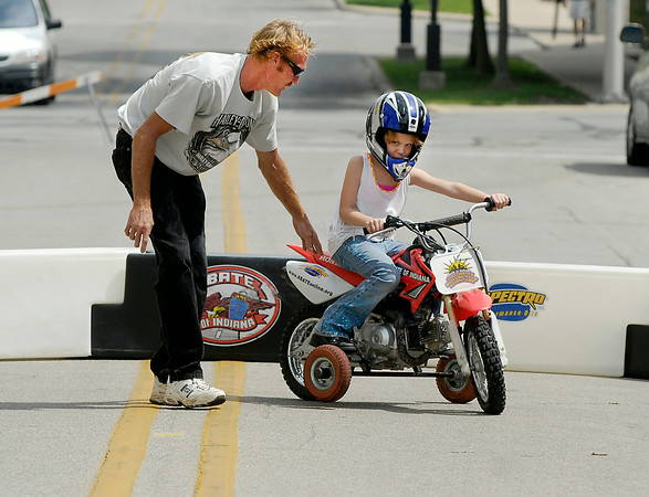 John P. Cleary | The Herald Bulletin<br /> Chloe Eastwood, 7, gets her first experience riding a motorcycle, with a little help from dad Chad Eastwood, at the ABATE of Indiana's Tiny Tots Motorcycle Adventure during the City Wide Community Day at Dickmann Town Square.