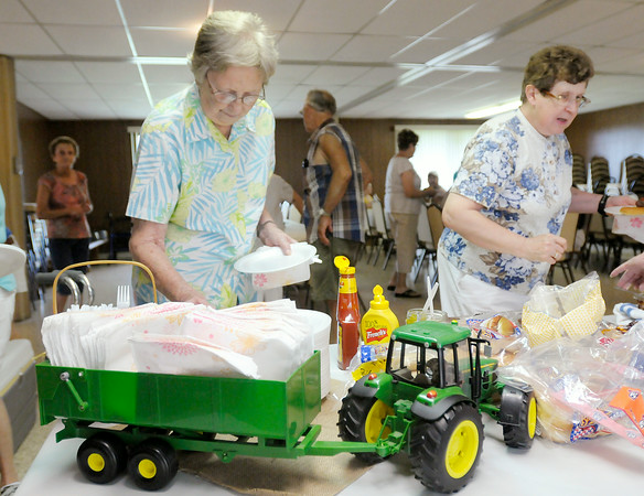 Don Knight | The Herald Bulletin<br /> A toy tractor serves as a napkin holder as members of Epworth United Methodist Church enjoy a meal together before a combine blessing on Saturday. Friday's rain made the church property too wet for heavy farm equipment but members carried on with toy tractors symbolically taking the place of the real ones as they prayed for a bountiful and safe harvest.