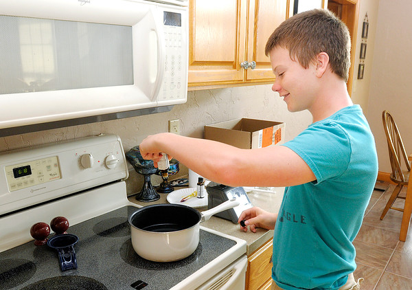 Don Knight | The Herald Bulletin<br /> Derek Sikorski, 13, adds drops of lavender oil to melted wax as he works on a batch of Pest Away Candles. The Chamber of Commerce is looking for more young entrepreneurs to take part in this year's YEA program.