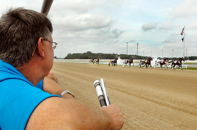 John P. Cleary | The Herald Bulletin Bob Bellamy watches his horse Red Scooter come by the grandstand the first time during the second race at Hoosier Park Saturday afternoon.