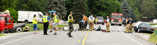 John P. Cleary | The Herald Bulletin<br /> Madison County Sheriff Department investigators  gather information at the scene of a fatal head-on collision involving a car, far right, and a flatbed truck, far left, in the 9100 block of North Indiana 37 near Elwood Thursday morning.<br /> The highway was closed for more then three hours as the investigation and cleanup were underway.