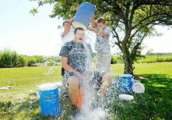 Don Knight | The Herald Bulletin<br /> From left, Jordan Crune and Jacob Price dump an bucket of ice water on Tanner Wise as he takes the ALS Ice Bucket Challenge at Madison-Grant on Friday.  To view or buy this photo and other Herald Bulletin photos, visit photos.heraldbulletin.com.
