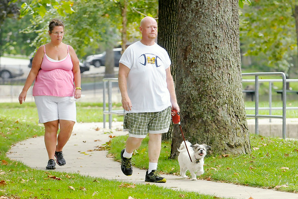 Don Knight   The Herald Bulletin<br /> Joe and Laura Neill walk their dog Maggie on Tuesday at Falls Park in Pendleton.Tuesday was National Dog Day. The day was originated by author Colleen Paige in 2004 to bring attention to dogs needing to be adopted and highlight how dogs improve our lives according to NationalDogDay.com.