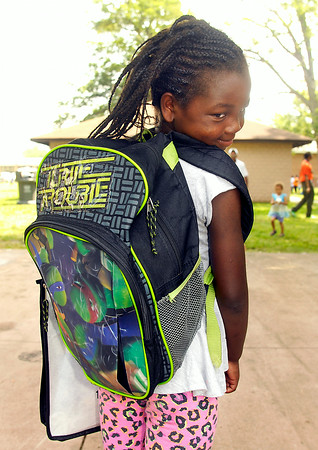 John P. Cleary | The Herald Bulletin<br /> E'mya Fuller, 7, shows off her backback at Ollie Dixon's Back to School Parade and Picnic Saturday as the 2nd grader prepared to go back to school.