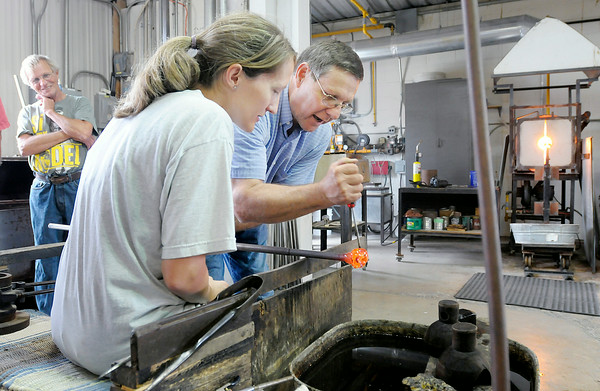 Don Knight | The Herald Bulletin<br /> Joe Rice and his daughter Amanda Plance make a glass paper weight at the House of Glass during the Elwood Glass Festival on Saturday. To view or buy this photo and other Herald Bulletin photos, visit photos.heraldbulletin.com.