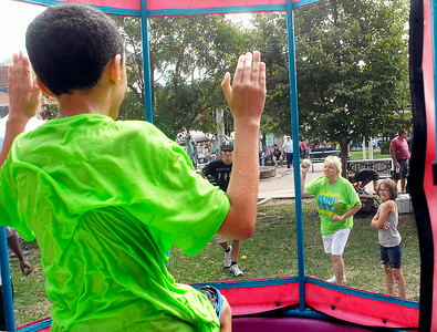 John P. Cleary | The Herald Bulletin Anthony Taliaferro, 8, yells at his grandmother Pam Mock as she tries to knock him off his seat and into the dunk tank Saturday during the City Wide Community Day at Dickmann Town Square.