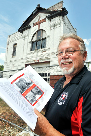 John P. Cleary | The Herald Bulletin<br /> Terry King, co-author of a book on the history of the Anderson Fire Department, stands in front of the old #4 fire station at 830 West 3rd Street holding his book to the page about the opening of this facility more then 111 years ago.