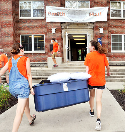 John P. Cleary   The Herald Bulletin<br /> AU student volunteers, junior Nancy Dalton, 21, and sophomore Kennedy Sade, 19, carry a large container into Smith Hall as they help incoming freshmen move in to their new home on campus Thursday.