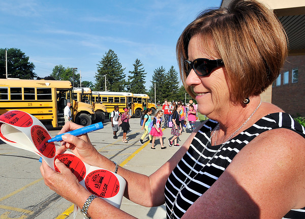 John P. Cleary   The Herald Bulletin<br /> Anderson Community Schools speech therapist Alexis Scherrer writes down bus numbers on big stickers to give students as they arrive for the first day of school at 10th Street Elementary School.