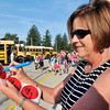 John P. Cleary | The Herald Bulletin<br /> Anderson Community Schools speech therapist Alexis Scherrer writes down bus numbers on big stickers to give students as they arrive for the first day of school at 10th Street Elementary School.