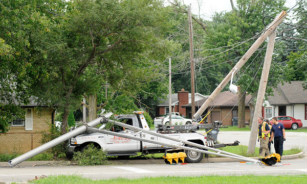 Don Knight | The Herald Bulletin<br /> A tow truck from Northwest Towing and Recovery hit a traffic signal and street light at the intersection of Raible Avenue and 25th Street on Friday. The driver was uninjured but waited inside the truck until first responders verified there were no live electrical wires on the ground or truck.