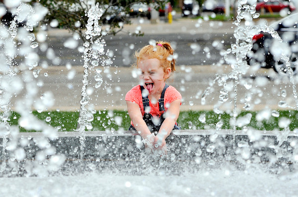 John P. Cleary   The Herald Bulletin<br /> Makenna Nunemaker, 4, has fun with the water spray from the fountain in Sesquicentennial Square at 14th & Main Streets Tuesday as she and her mother, Jeri Keesling, stopped at the park after being at the Anderson Public Library. The family lives in Markleville.