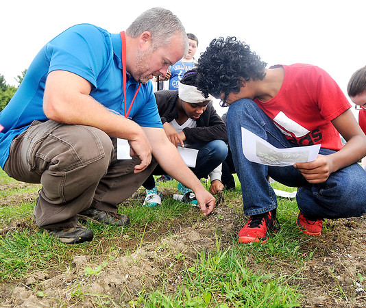 John P. Cleary | The Herald Bulletin<br /> Highland Middle School teacher Andy McCammon  shows students some of the growth that has happened during his new agriculture class.