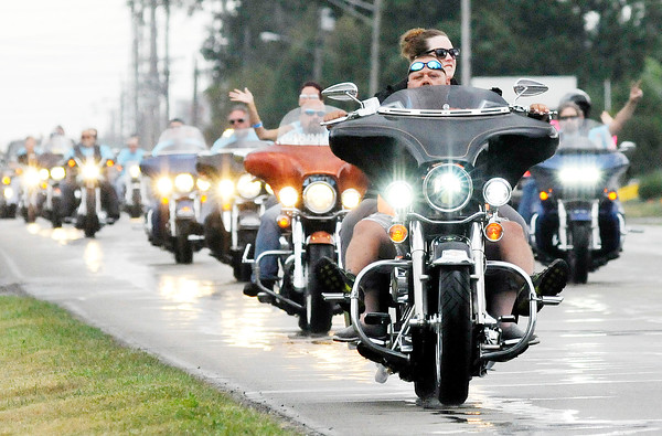 Don Knight | The Herald Bulletin<br /> Jessica and Lynsey Memorial Ride passes under an American flag while traveling on 53rd Street on Saturday. Proceeds benefit scholarships in memory of Jessica Lyons and Lynsey Schildmeier.